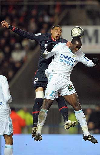 Guillaume Hoarau, del PSG, salta con Souleymane Diawara, del Olympique de Marsella.