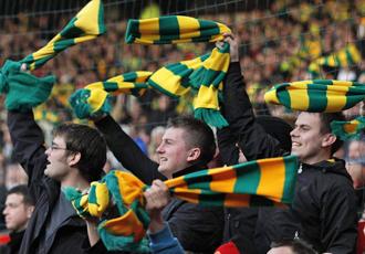Seguidores del United ondean sus bufandas a rayas verdes y amarillas durante un partido en Old Trafford.