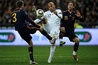 Henry intenta controlar el bal�n en pugna con Piqu� y Sergio Ramos.