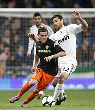 Mata conduce la pelota en presencia de Xabi Alonso.