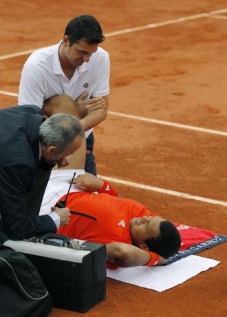 Tsonga es atendido en pista por el fisio de la ATP.