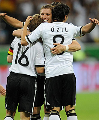 Lahm, Schwensteiger y �zil se abrazan tras uno de sus goles ante Bosnia