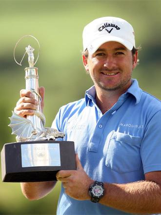 McDowell, posa sonriente con su trofeo.