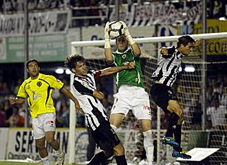 Calatayud ataja con seguridad el bal�n ante el acoso de Mariano S�nchez y De Lucas durante el empate del H�rcules ante el Cartagena de este domingo