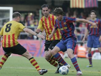Un jugador del Barça B trata de superar la poblada defensa visitante