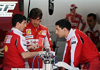 Alonso habla con dos de sus ingenieros.