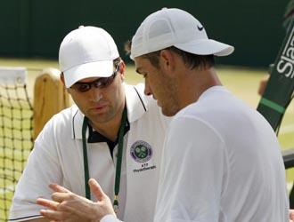 Isner siendo atendido por el fisio del torneo en su partido contra De Bakker