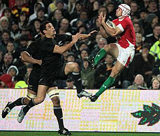 El ala gal�s Leigh Halfpenny coge el oval en el aire ante la presi�n de Dan Carter y otro jugador neoceland�s