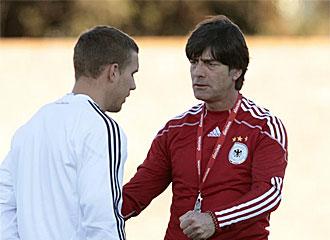 Podolski charla con L�w durante el entrenamiento.