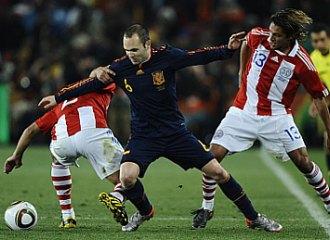 Andr�s Iniesta trata de de zafarse del marcaje de dos jugadores paraguayos.