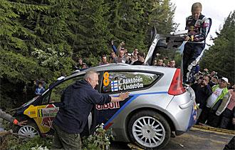 Lindstrom, copiloto de Raikkonen, ayudando con su peso a la gr�a a sacar el coche del precipicio