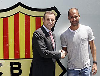 Sandro Rossell y Pep Guardiola se estrechan la mano tras rubricar el contrato.