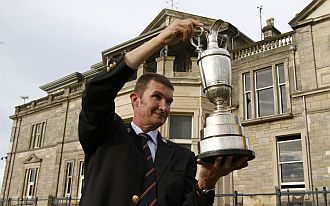 Un miembro de la Casa Club de St Andrwes sostiene la Jarra de Clarete, trofeo que levanta el ganador.