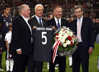 Beckenbauer recibe una camiseta en un partido para homenajearle.