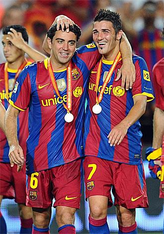 Villa y Xavi se abrazan tras recoger las medallas que les acreditan como campeones de esta Supercopa.