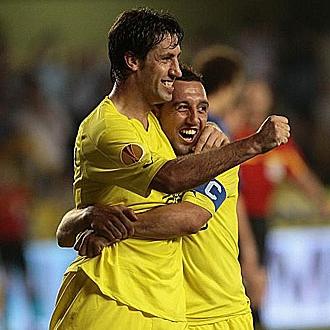 Capdevila celebra un gol junto con Cazorla