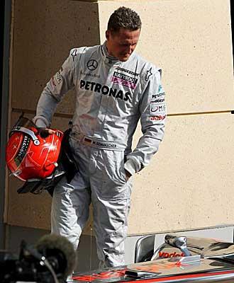 Michael Schumacher observando un coche McClaren.
