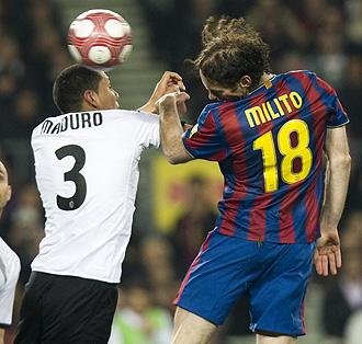 Milito y Maduto luchan un bal�n en el Bar�a-Valencia de la temporada pasada.