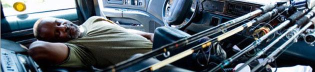 Ray Williams durmiento en un coche, junto a sus cañas de pescar (Boston Globe)