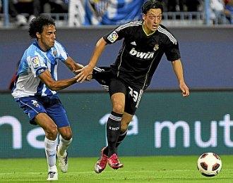 Mesut �zil trata de zafarse de un contrario en el M�laga-Real Madrid de este s�bado en La Rosaleda.