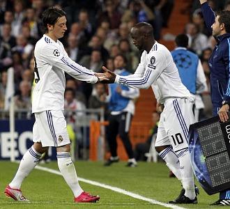 �zil y Lass se chocan las manos tras un cambio realizado por Mourinho.