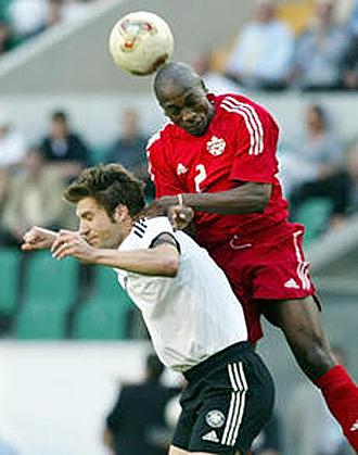 Nsaliwa se eleva por encima del alemán Torsten Frings en un partido de la selección de Canadá