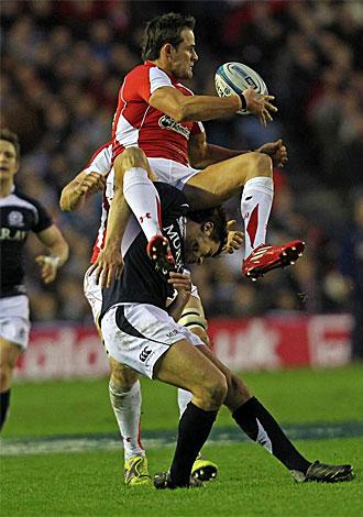 El escoc�s Hugo Southwell trata de evitar que el gal�s Lee Byrne atrape con comodidad el bal�n.