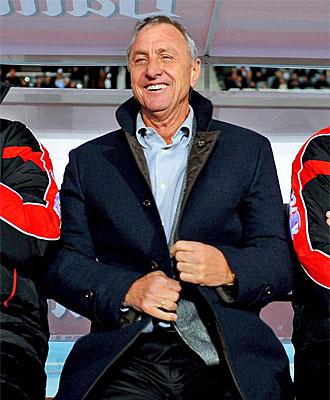Cruyff sonr�e en un banquillo.