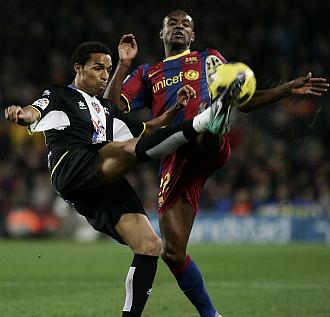 Valdo y Abidal disputan un bal�n en el partido de la primera vuelta.