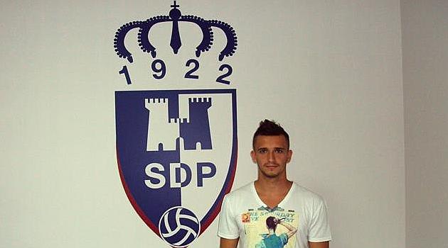 Dinu Molvodan posa delante del escudo de su nuevo equipo / Web de la Ponferradina
