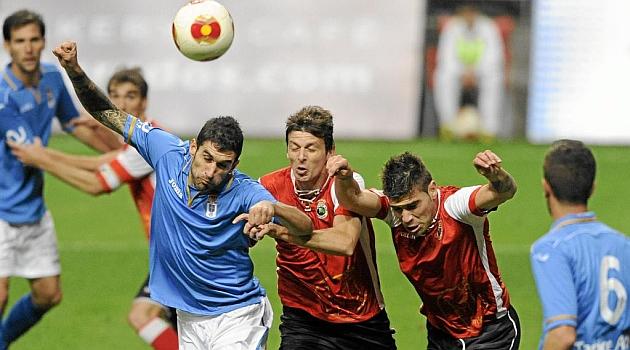 Dos jugadores el Racing le disputan un bal�n a uno del Oviedo. JAVIER GARC�A
