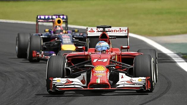 Fernando Alonso (32), con Sebastian Vettel (27), en la carrera celebrada ayer en el circuíto de Interlagos. / AFP