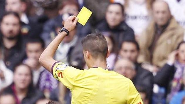 Árbitro sacando una tarjeta amarilla. Foto: Ángel Rivero