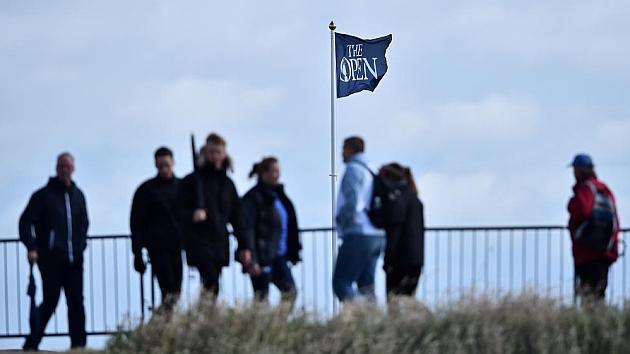 La gente camina frente a la bandera que ondea debido a las ráfagas que suspendieron el juego en St Andrews