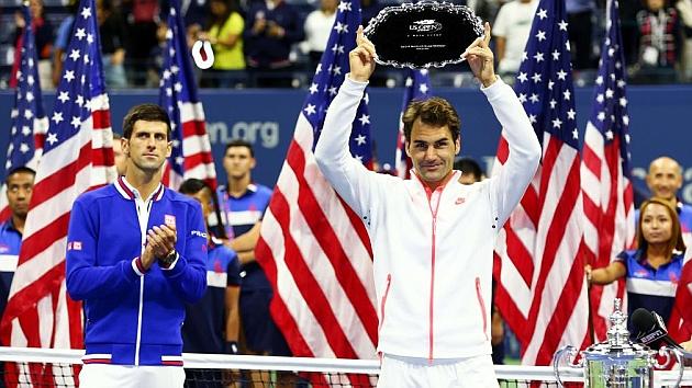 Federer levanta el trofeo de subcampeón del US Open ante los aplausos de Djokovic.