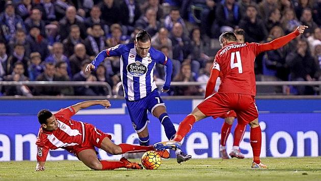 Lucas Pérez intenta llevarse el balón entre dos jugadores del Sevilla.