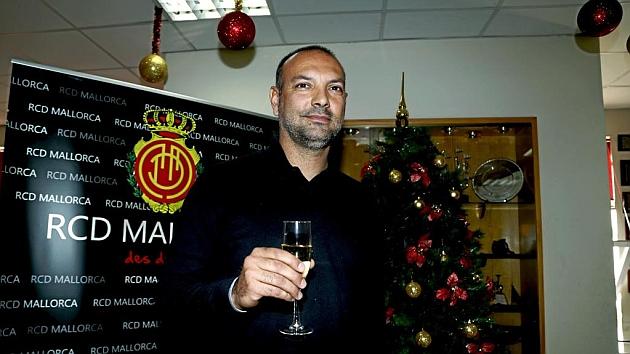 Pepe Gálvez brinda con una copa de sidra delante de un árbol de Navidad y un escudo del Mallorca