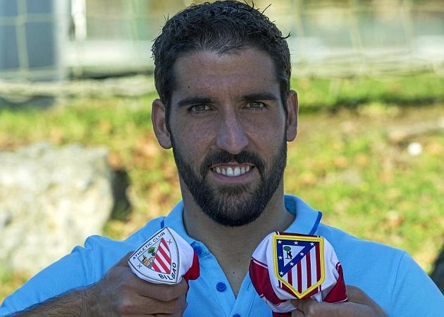 Raúl García muestra los escudos de Athletic y Atlético, su actual equipo y el equipo al que perteneció durante nueve campañas.